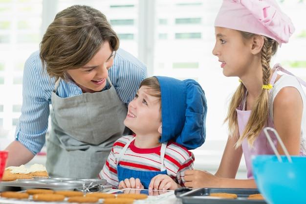 Lachende moeder en kinderen interactie met elkaar tijdens het bereiden van cookies