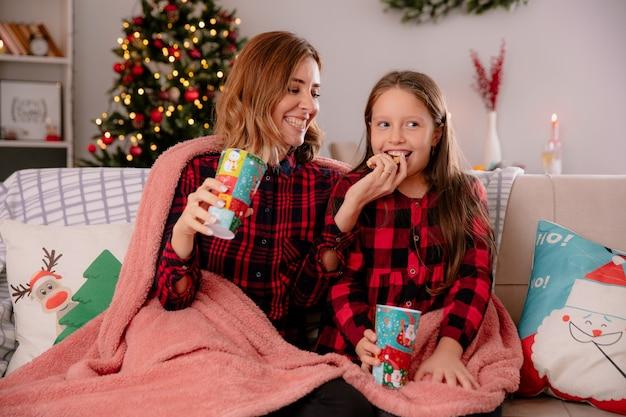 Lachende moeder houdt papieren beker vast en voedt dochter met koekje zittend op de bank bedekt met deken en geniet thuis van de kersttijd