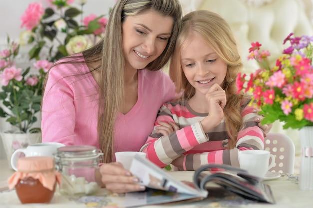 Lachende moeder met dochtertje die thee drinkt met tijdschrift in de keuken