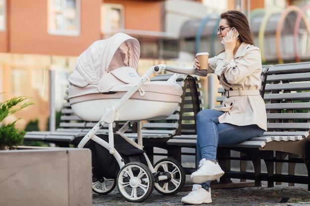 Lachende moeder met een pasgeboren baby in een kinderwagen drinkt thee of koffie op straat
