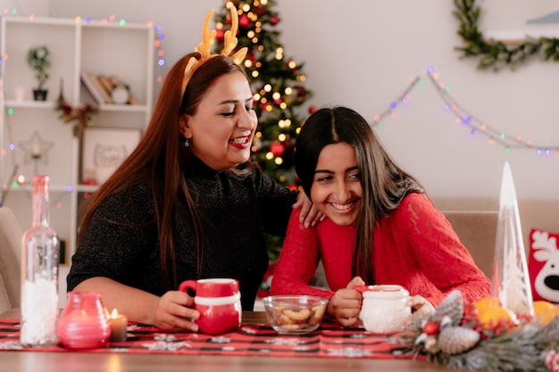 Lachende moeder met rendieren hoofdband kijkt naar haar dochter zittend aan tafel genieten van de kersttijd thuis