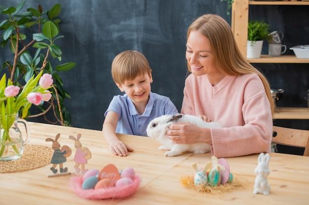Lachende moeder pluizig konijn aaien samen met opgewonden zoon tijdens het vieren van pasen