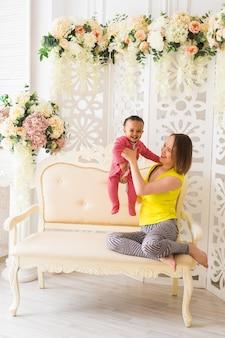 Lachende moeder spelen met zoontje thuis.