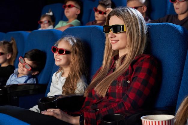 Lachende moeder zit met dochtertje in de bioscoop