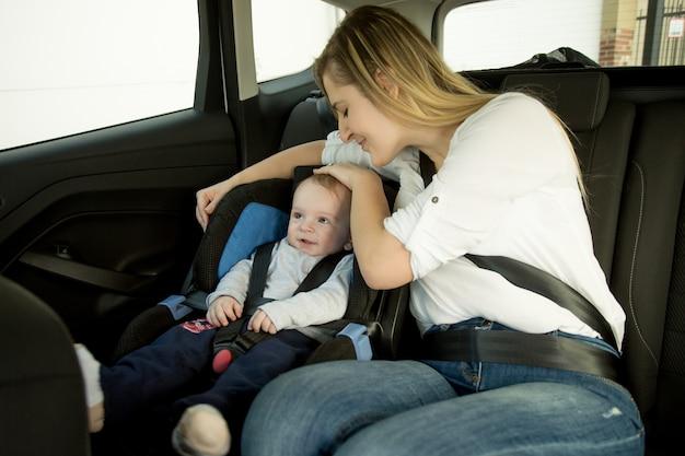 Lachende moeder zittend op de achterbank van de auto met haar baby
