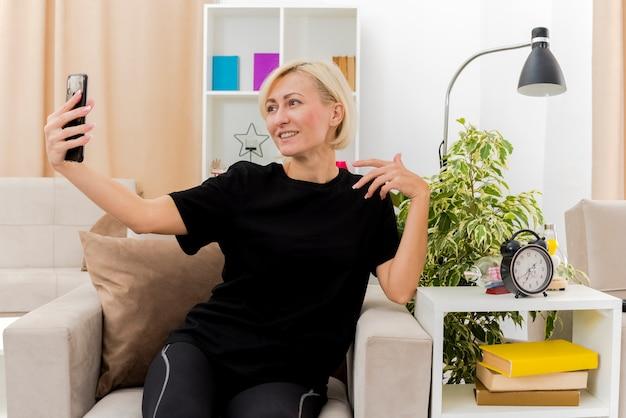 Lachende mooie blonde russische vrouw zit op fauteuil houden en kijken naar telefoon in de woonkamer