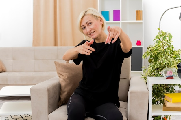 Lachende mooie blonde russische vrouw zit op fauteuil wijzend op camera met twee handen in de woonkamer