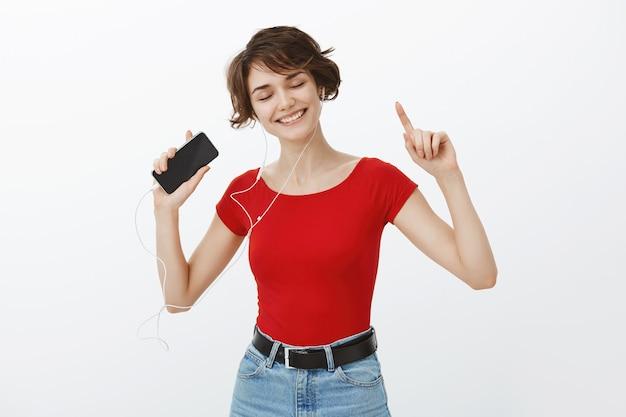 Lachende mooie brunette vrouw zorgeloos dansen, muziek luisteren en dansen in oortelefoons, smartphone te houden