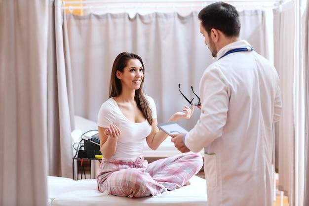 Lachende mooie brunette zittend op het bed met gekruiste benen en praten met de arts. arts in wit uniform luistert naar haar en houdt tablet.