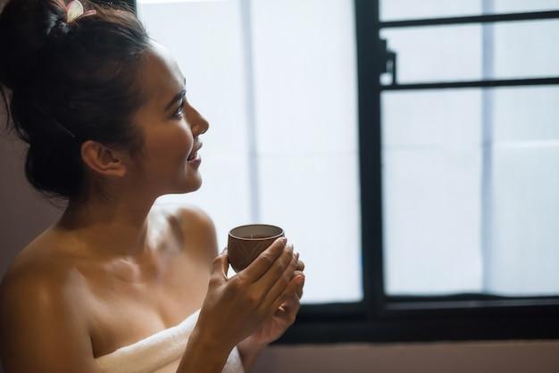 Lachende mooie jonge aziatische vrouw in het wit houdt een kopje hete thee vast na een thaise massage in de spa