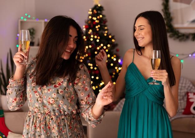 Lachende mooie jonge meisjes houden glazen champagne genieten van kersttijd thuis