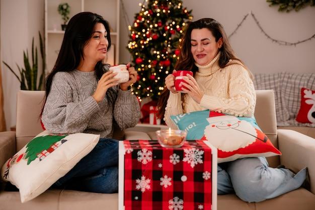 Lachende mooie jonge meisjes houden kopjes vast terwijl ze op fauteuils zitten en thuis genieten van kersttijd