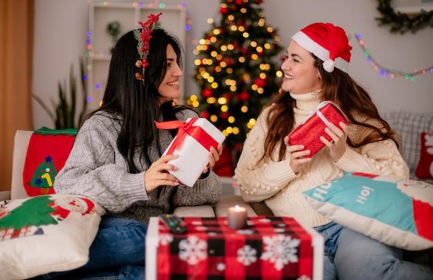 Lachende mooie jonge meisjes met kerstmuts en holly krans houden geschenkdozen en kijken elkaar zittend op fauteuils en genieten van kersttijd thuis