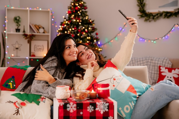 Lachende mooie jonge meisjes nemen selfie zittend op fauteuils en genieten van kersttijd thuis