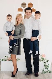 Lachende mooie jonge ouders en hun kinderen kijken naar de camera terwijl ze poseren tegen een witte muur. familie en ouderschap concept