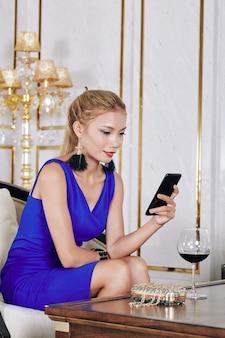 Lachende mooie jonge vrouw berichten in haar smartphone controleren bij het drinken van een glas wijn