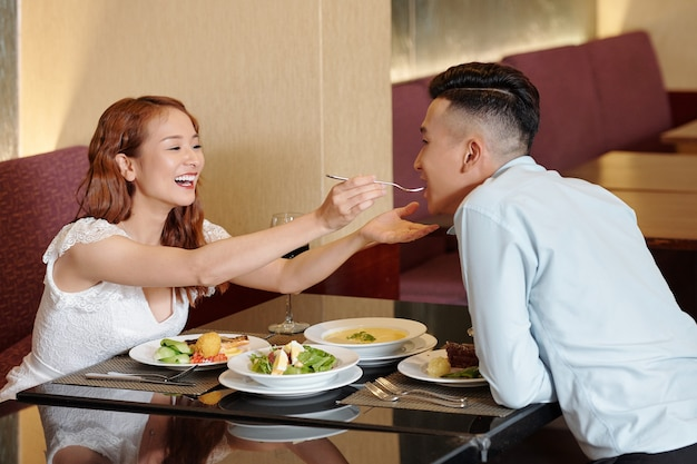 Lachende mooie jonge vrouw die haar vriend voedt met een gerecht dat ze zelf in het restaurant heeft besteld