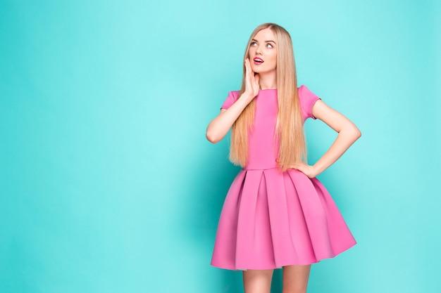 Lachende mooie jonge vrouw in roze mini jurk poseren, iets presenteren en wegkijken.