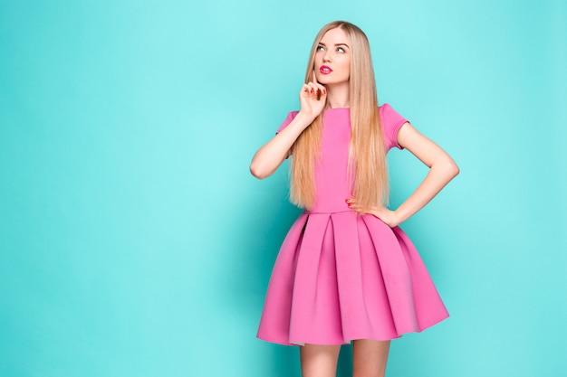 Lachende mooie jonge vrouw in roze mini jurk poseren, iets presenteren en wegkijken