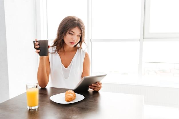 Lachende mooie jonge vrouw met behulp van tablet en thuis ontbijten