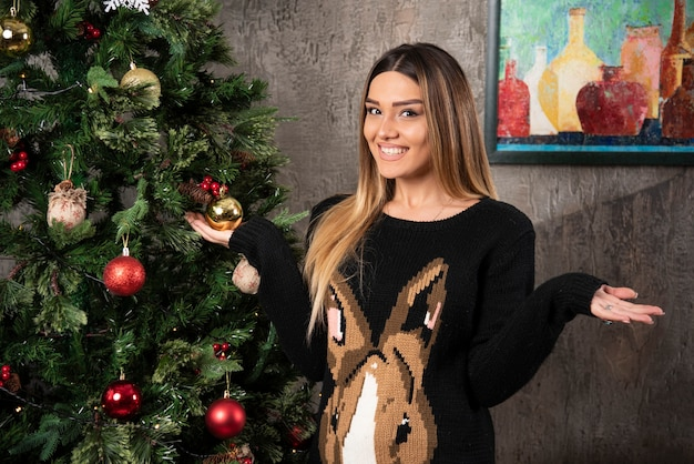 Lachende mooie vrouw in warme trui poseren met handen in de buurt van de kerstboom. hoge kwaliteit foto