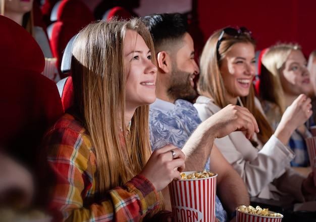 Lachende mooie vrouw kijken naar film.