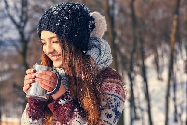 Lachende mooie vrouw met kop warme drank staande in de buurt van winter woud en vakanties doorbrengen onder het prachtige winterlandschap