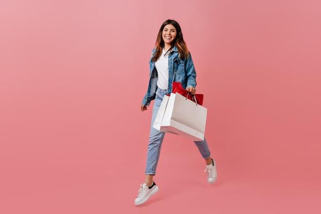 Lachende mooie vrouw met winkel tas. meisje in denimkleren die op roze achtergrond stellen.