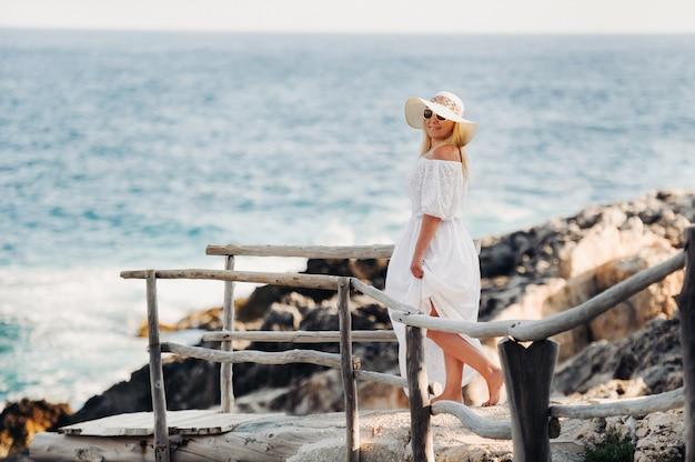 Lachende mooie vrouw op het strand in een strooien hoed op het eiland zakynthos.