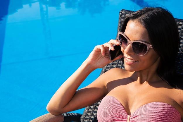 Lachende mooie vrouw praten aan de telefoon op ligstoel buitenshuis