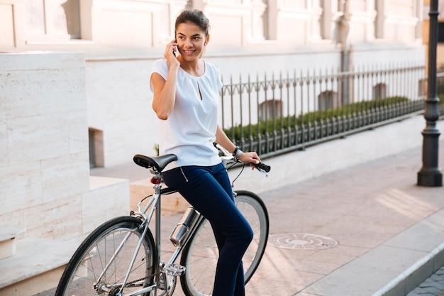 Lachende mooie vrouw praten over de telefoon leunend op de fiets op straat