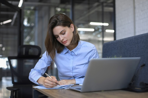 Lachende mooie vrouw zit aan tafel. gelukkig ondernemer schrijft notities aan klanten.