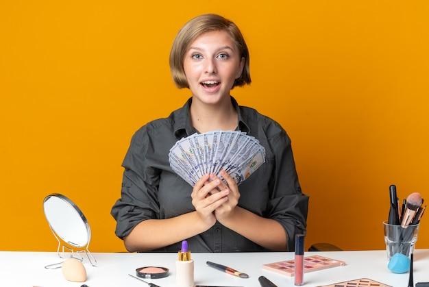 Lachende mooie vrouw zit aan tafel met make-up tools met contant geld
