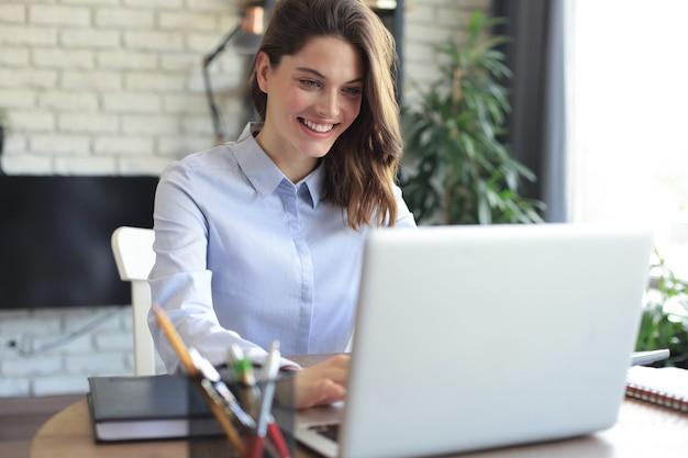 Lachende mooie vrouw zittend aan tafel, kijkend naar het scherm van de laptop. gelukkige ondernemer die bericht-e-mail leest met goed nieuws, online chat met klanten.
