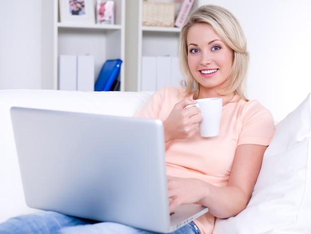 Lachende mooie vrouw zittend op de bank met laptop en kopje koffie
