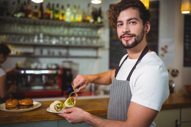 Lachende ober met een plaat van plantaardige roll in cafã ©