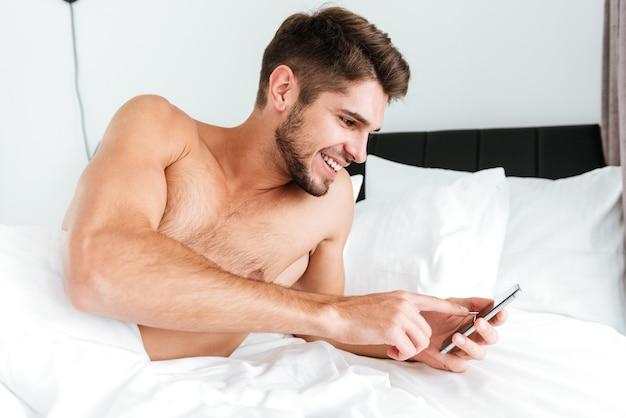 Lachende ontspannen jonge man liggend en met behulp van mobiele telefoon in bed
