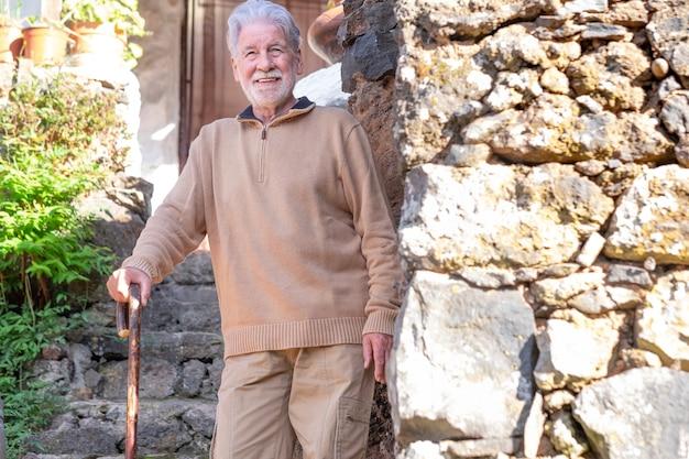 Lachende oude senior man in winter trui buiten van een landelijk huis leunend op wandelstok. blanke man met baard en wit haar