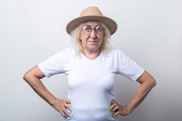 Lachende oude vrouw in een hoed hand in hand op een riem op een lichte achtergrond.