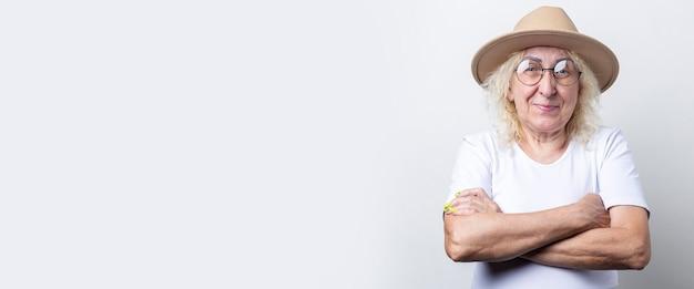 Lachende oude vrouw in hoed met haar armen gekruist op een lichte achtergrond. banier.