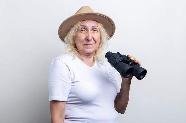 Lachende oude vrouw met verrekijker op een lichte achtergrond.