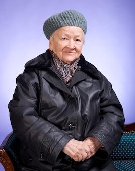 Lachende oude vrouw zittend op een stoel op een lila achtergrond
