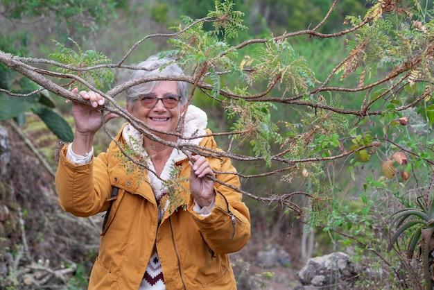 Lachende oudere vrouw buitenshuis op bergwandeling met wintertrui en gele jas. ontspannen volwassen vrouw die een boomtak aanraakt en naar de natuur kijkt