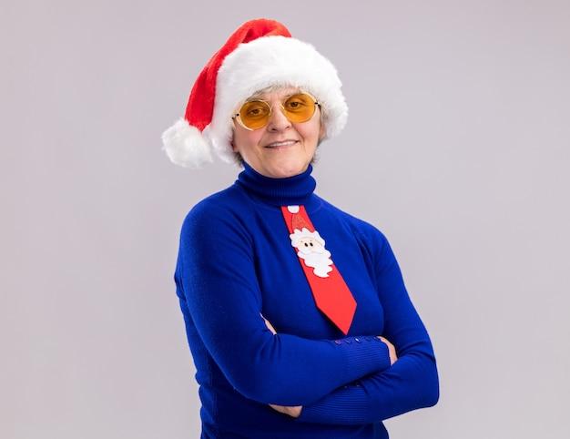 Lachende oudere vrouw in zonnebril met kerstmuts en kerst stropdas staan met gekruiste armen geïsoleerd op een witte achtergrond met kopie ruimte