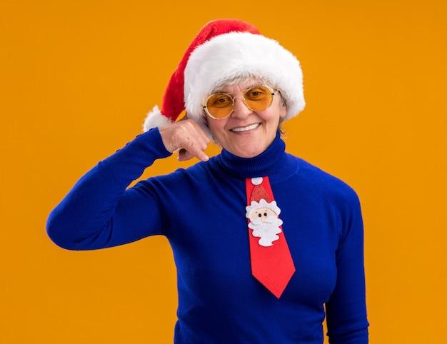 Lachende oudere vrouw in zonnebril met kerstmuts en kerstman stropdas gebaren bel me teken geïsoleerd op een oranje achtergrond met kopie ruimte