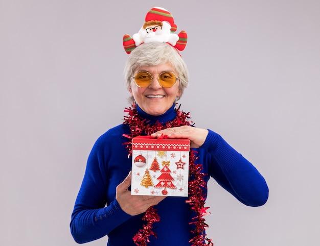 Lachende oudere vrouw in zonnebril met santa hoofdband en slinger om de nek houdt de doos van de gift van kerstmis geïsoleerd op een witte muur met kopie ruimte