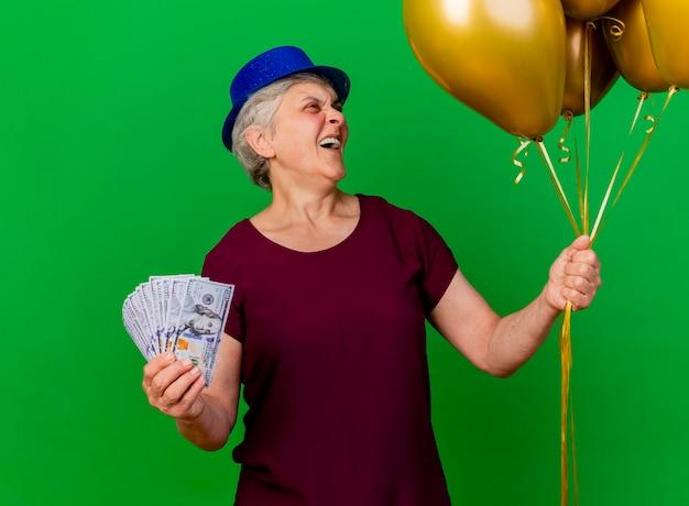Lachende oudere vrouw met feestmuts houdt geld vast en kijkt naar helium ballonnen op groen