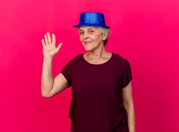 Lachende oudere vrouw met feestmuts staat met opgeheven hand op roze