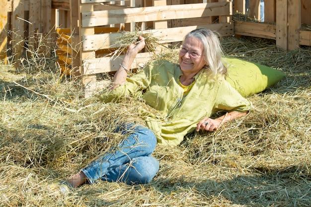 Lachende oudere vrouw rust op hooizolder en gooit voor de grap hooi naar iemand