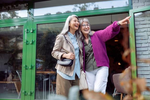 Lachende oudere vrouw wijst naar iets dat bij een aziatische vriend in de buurt van café staat